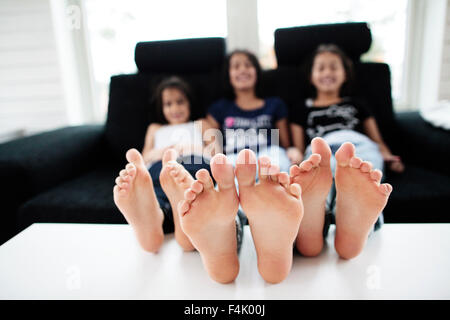 Girls sitting on sofa and smiling - Stock Photo