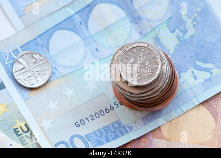 British five silver pence coin on a pile of coins and twenty  Euro notes - Stock Photo