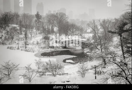 Central Park's Pond and Gapstow Bridge during a snowstorm. Quiet winter scene in the heart of Manhattan, New York - Stock Photo
