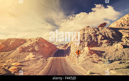 Old film retro stylized rocky desert road, USA. - Stock Photo