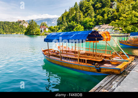 Wooden Tourist Boat on Shore of Bled Lake, Slovenia with Bled Castle in Background - Stock Photo