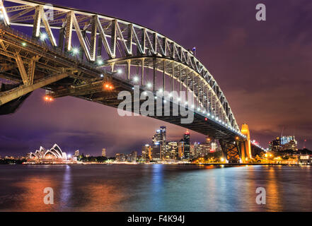 East side of Sydney harbour bridge at sunset with bright illumination of steel arch and columns reflecting in the - Stock Photo