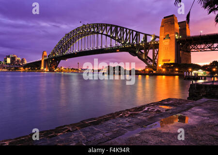 Sydney harbour bridge side view from Milsons point after fresh rain when brightly illuminated bridge arch and column - Stock Photo