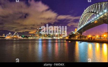 Australia Sydney city CBD cityline across harbour with sky-scrapers, opera and harbour bridge at sunset fully illuminated