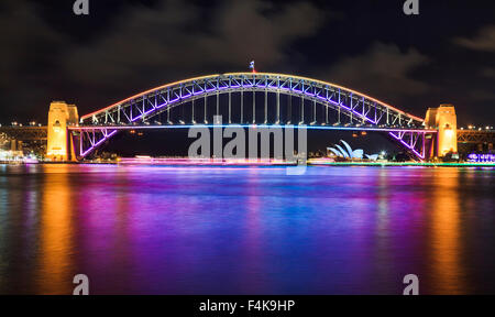 Australia Sydney Harbour Bridge side view of illuminated arch after sunset with bright refiection of the lights - Stock Photo
