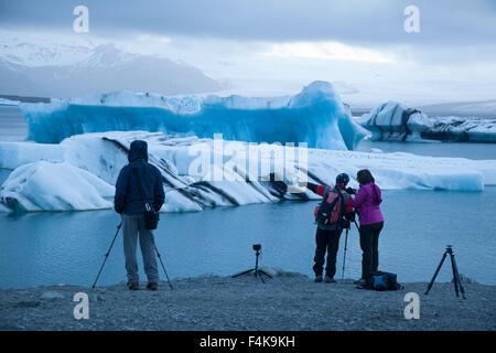 Photographers on the shore of Jokulsarlon glacial lagoon, Vatnajokull National Park, Sudhurland, Iceland. - Stock Photo