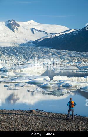 Person beside Fjallsarlon iceberg lagoon, beneath Fjallsjokull glacier. Vatnajokull National Park, Sudhurland, Iceland. - Stock Photo