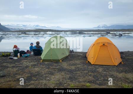 Family camping beside Fjallsarlon iceberg lagoon, Vatnajokull National Park, Sudhurland, Iceland.