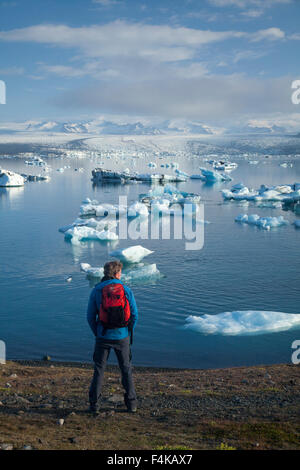 Hiker on the shore of Jokulsarlon iceberg lagoon, Vatnajokull National Park,  Sudhurland, Iceland. - Stock Photo