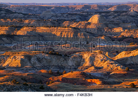 The badlands of Theodore Roosevelt National Park, North Dakota, are turned red at sunset at Painted Canyon. - Stock Photo
