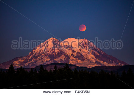 The full moon in a type of lunar eclipse known as a Super Blood Moon rises over Mount Rainier in Washington state. - Stock Photo