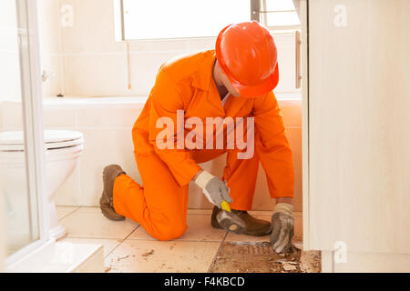 construction worker removing old floor tiles using a hammer and chisel - Stock Photo