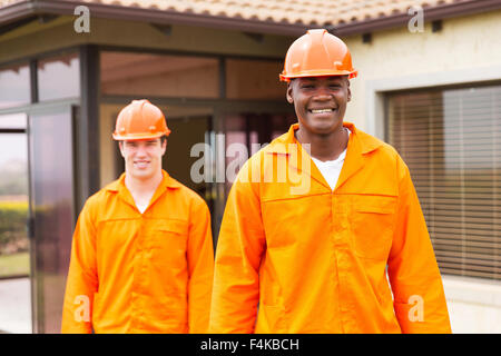 smiling African handyman standing in front of colleague before house renovation - Stock Photo