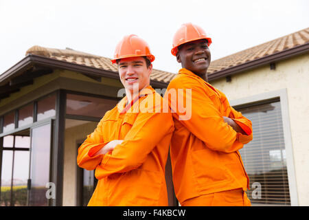 portrait of handsome contractors standing in front of house - Stock Photo