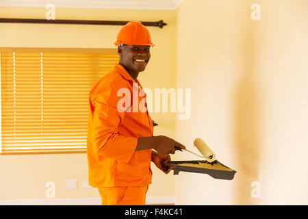 happy African contractor painting inside the house - Stock Photo
