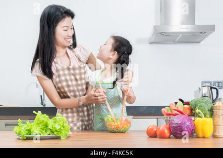 family, children and happy people concept - Asian mother and kid daughter cooking in the kitchen at home - Stock Photo