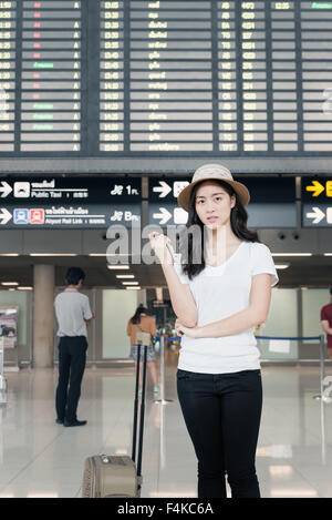 Pretty Asian young female passenger at the airport.(color toned image) - Stock Photo