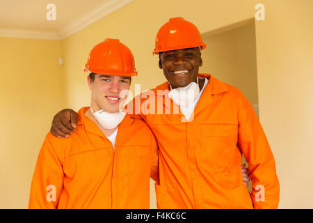 multiracial craftsmen standing in a house during renovation - Stock Photo