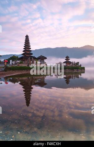 Ulun Danu temple during sunrise in Beratan Lake in Bali Indonesia. - Stock Photo
