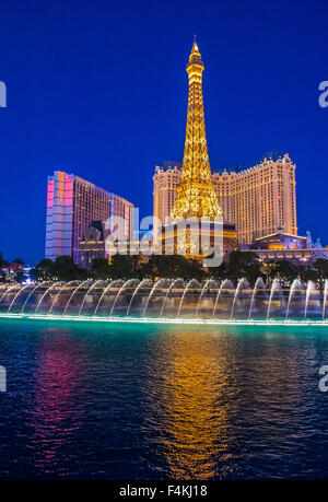 Night view of the dancing fountains of Bellagio and the Eiffel Tower replica of Paris hotel in Las Vegas - Stock Photo