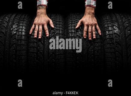 Men's hands on a car tires, studio shot - Stock Photo