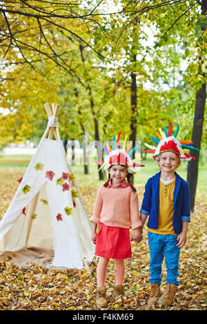 Happy girl and boy in Indian headdresses playing in autumn park - Stock Photo