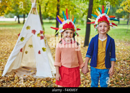 Little girl and boy in Indian headdresses looking at camera in autumn park - Stock Photo