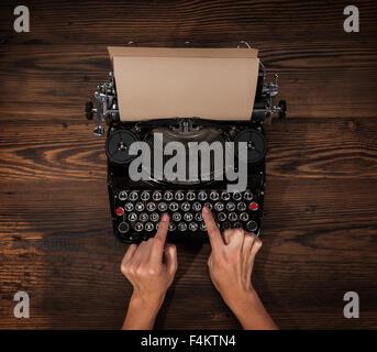 Woman typing on an old typewriter - Stock Photo