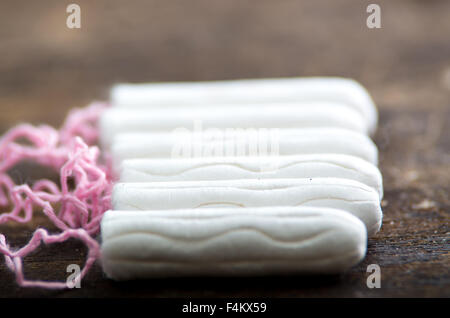 Clean white tampons lying on wooden surface - Stock Photo