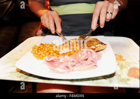 Woman eating baked beans on toast with slice of ham and a poached egg TV dinner on tray on her lap - Stock Photo
