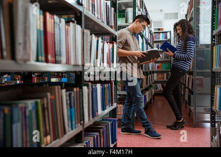 Portrait of a young students reading books in library - Stock Photo