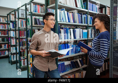 Portrait of a happy students speaking in library - Stock Photo