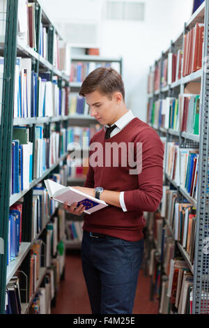 Portrait of a handsome man reading book in university library - Stock Photo