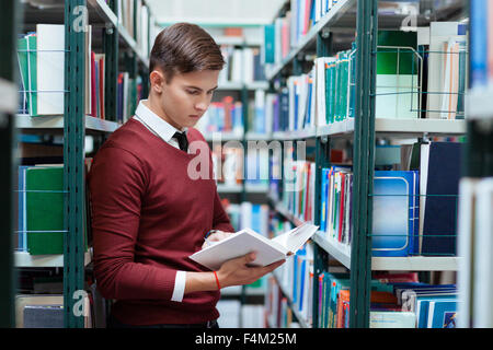 Portrait of a young female student searching book in university library - Stock Photo