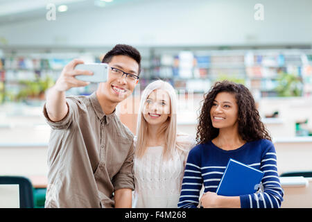 Smiling multi ethnic students making selfie photo on smartphone in the university library - Stock Photo