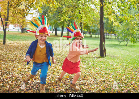 Cute girl and boy in Indian headdresses running in autumn park - Stock Photo