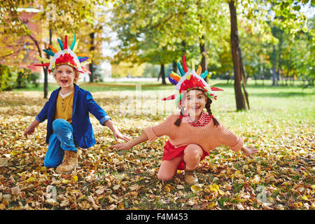 Cheerful girl and boy in Indian headdresses playing outdoors - Stock Photo