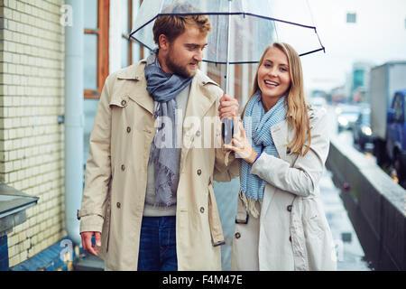 Amorous man and woman walking under umbrella - Stock Photo