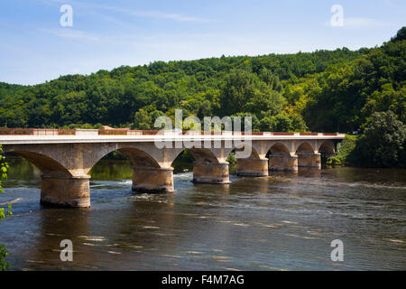 The arched road bridge over the river Dordogne at Lalinde in France - Stock Photo
