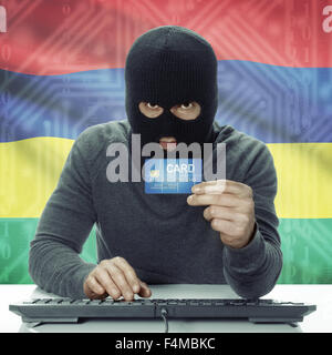 Dark-skinned hacker with credit card in hand and flag on background - Mauritius - Stock Photo