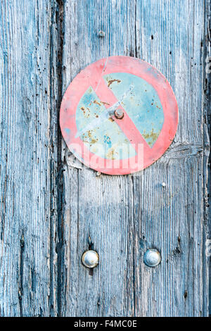 An old wooden door with a faded no parking sign on it in Provence France - Stock Photo