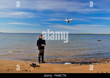 Young man operating drone helicopter on shore of Ennadi Lake, Arctic Haven Lodge, Nunavut, Canada - Stock Photo