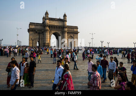 The Gateway of India in the suburb Colaba with many people visiting the famous place - Stock Photo