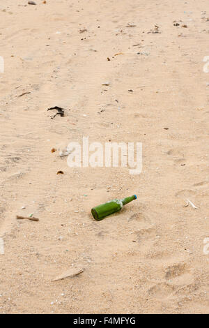 Broken bottles and other garbage lying scattered on a beach. - Stock Photo