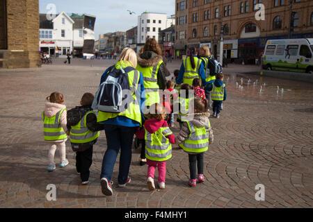 Safeguarding Pre-School primary children wearing protective fluorescent hi-vis hazard jackets on walk around Blackpool - Stock Photo