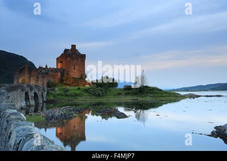The beautiful Eilean Donan Castle, Scotland with reflections in Loch Duich at Sunset - Stock Photo