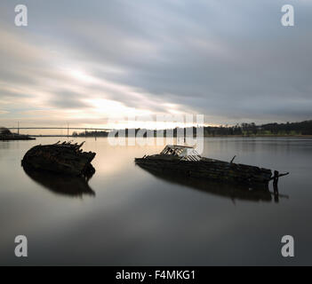 Shipwrecks by Bowling Harbour with Erskine Bridge in the background at Sunset - Stock Photo