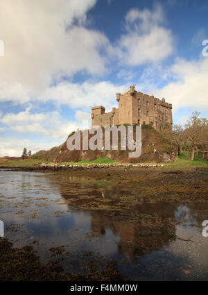 Reflections of Dunvegan Castle in Loch Dunvegan on a sunny day - Stock Photo