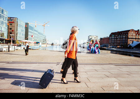 Side view of businesswoman with luggage walking on city street - Stock Photo