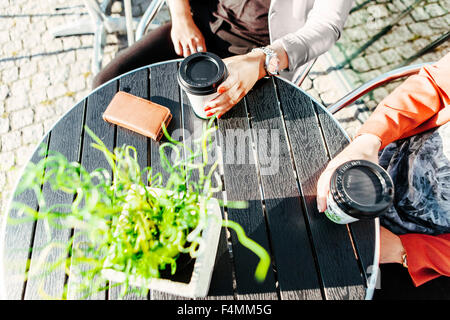 Cropped image of businesswomen holding disposable cups at sidewalk cafe table - Stock Photo